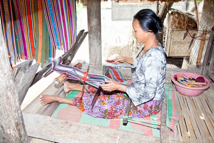 An elderly weave songket (traditional colorful fabric) using the classic loom in Sade,Lombok. Sade village is famous for their beautiful cloth