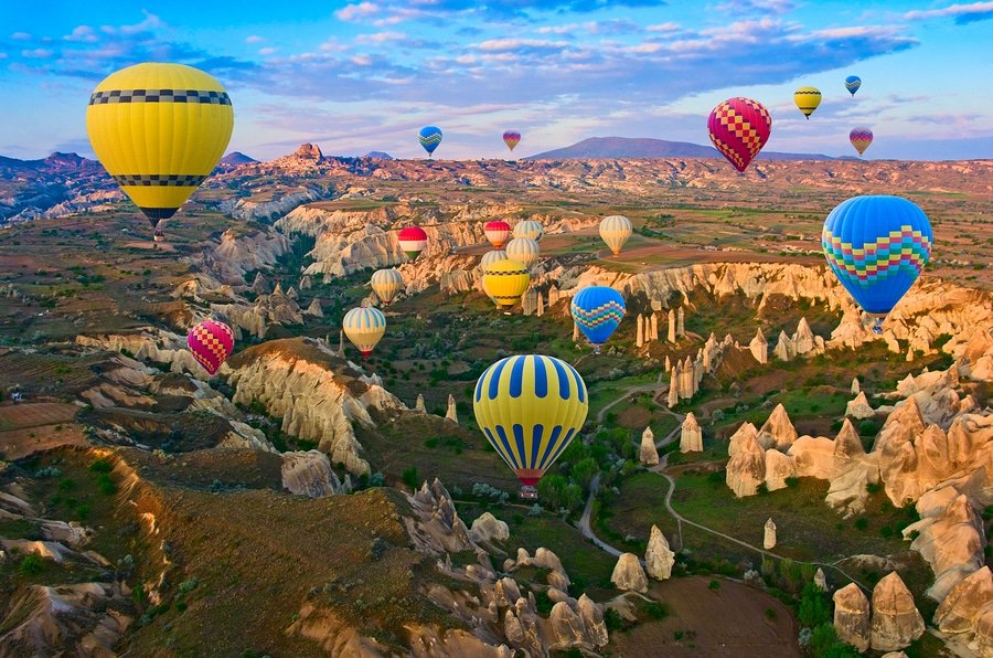 Hot air balloons flying over spectacular landscape of fairy chimneys carved in volcanic tuff by erosion, Cappadocia, Turkey