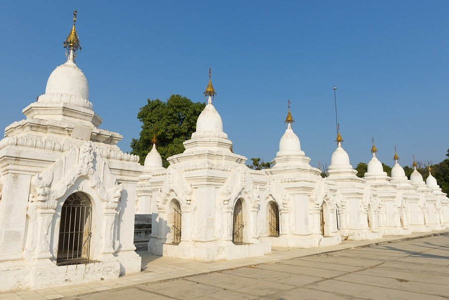 Kuthodaw Pagoda contains the worlds biggest book. There are 729 white stupas with caves with a marble slab inside - page with Buddhist inscriptions