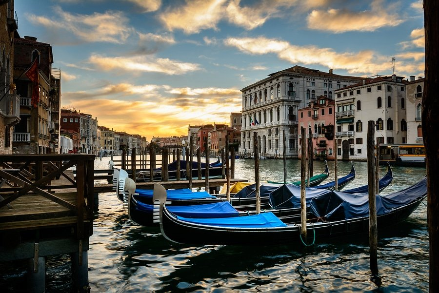 Gondolas or boats on Grand canal at sunset in beautiful town Venice